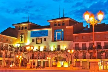 Plaza Mayor de Torrejón de Ardoz en el momento de anochecer con el Ayuntamiento y la Iglesia San Juan Evangelista de fondo.